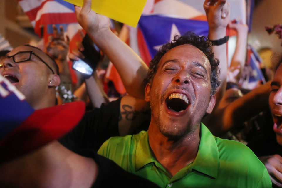SAN JUAN, PUERTO RICO - JULY 24: People celebrate after news that Gov. Ricardo Rossello is stepping down on July 24, 2019 in Old San Juan, Puerto Rico. Protesters had been demanding that the governor step down after a group chat was exposed that included misogynistic and homophobic comments allegedly made between Rosselló and top aides.  (Photo by Joe Raedle/Getty Images)