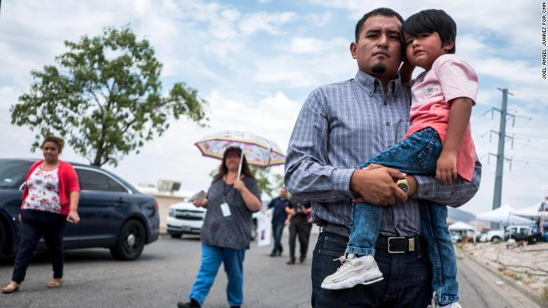 """Ivan Flores, 27, an insurances broker in El Paso, Derek, 4, pose for a portrait near the site of the Walmart shooting in El Paso, Texas, Tuesday, Aug. 6, 2019. """"The people that were targeted were people that look just like me,"""" said Flores. """"I have a six-month old [child] at home...I don't know what my family would be going through if they lost me and his mom just like three kids lost their parents here."""""""
