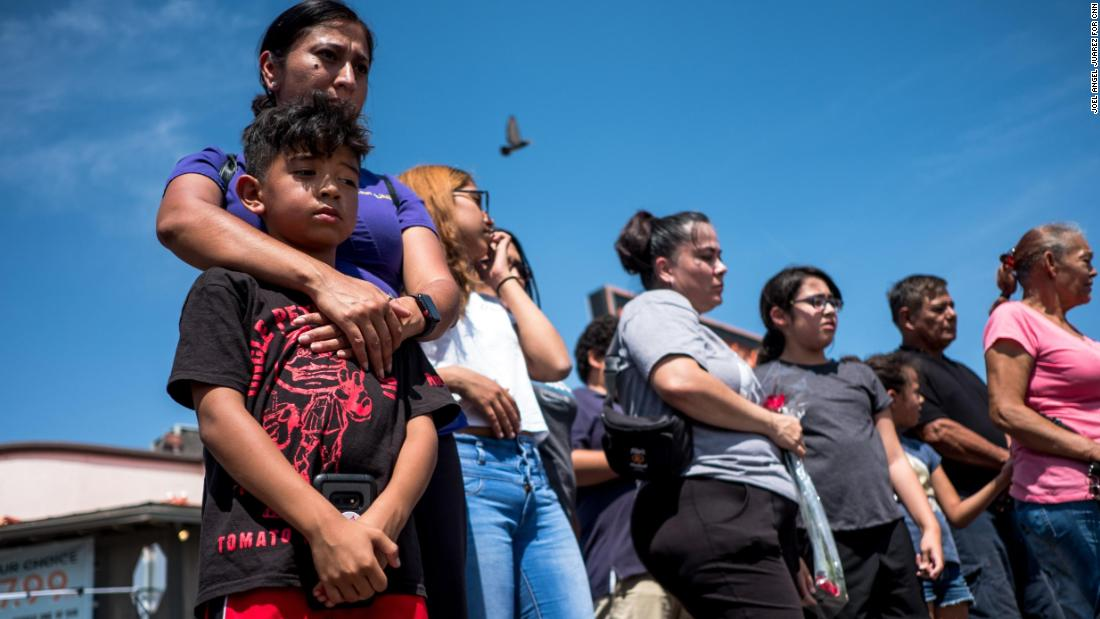 Tony Casta??eda, 8, left, is embraced by his mother Alma Casta??eda, 42, as they visit a memorial near the site of the Walmart shooting in El Paso, Texas, Tuesday, Aug. 6, 2019.