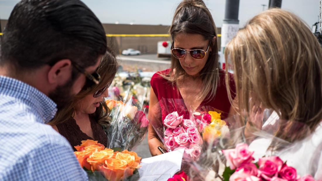 """Claudia Portillo, 52, second from right, prays near the site of the Walmart shooting in El Paso, Texas, Tuesday, Aug. 6, 2019. Portillo, an employee at a genetic lab, fled Ciudad Ju??rez with her two children after her husband was killed, looking to start a new life in El Paso over two decades ago. """"We don't see hate crimes out here,"""" Portillo said. """"I'm reliving those memories of living in Ju??rez back in the 90s. You are looking behind your back all the time, that's what I caught myself doing."""""""