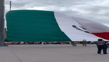 Civiles ayudan a militares con la bandera mexicana