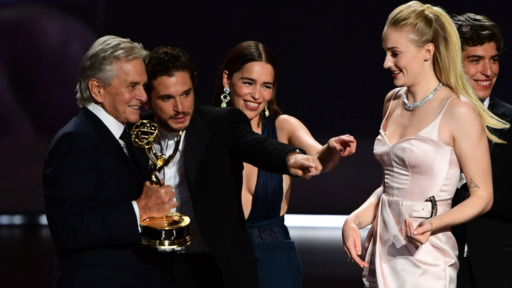 """(From L) Michale Douglas, British actor Kit Harington, British actress Emilia Clarke and British actress Sophie Turner gesture as cast and crew of """"Game of Thrones"""" accepts the Outstanding Drama Series award onstage during the 71st Emmy Awards at the Microsoft Theatre in Los Angeles on September 22, 2019. (Photo by Frederic J. BROWN / AFP) (Photo credit should read FREDERIC J. BROWN/AFP/Getty Images)"""