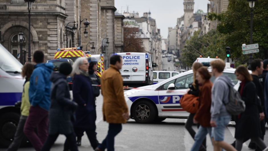 Passerby walk as police vehicle drive toward Paris prefecture de police (police headquarters) after three persons have been hurt in a knife attack on October 3, 2019. - A knife attacker was shot and injured after hurting two people at police headquarters in the historical centre of Paris on October 3, sources told AFP. (Photo by Martin BUREAU / AFP) (Photo by MARTIN BUREAU/AFP via Getty Images)