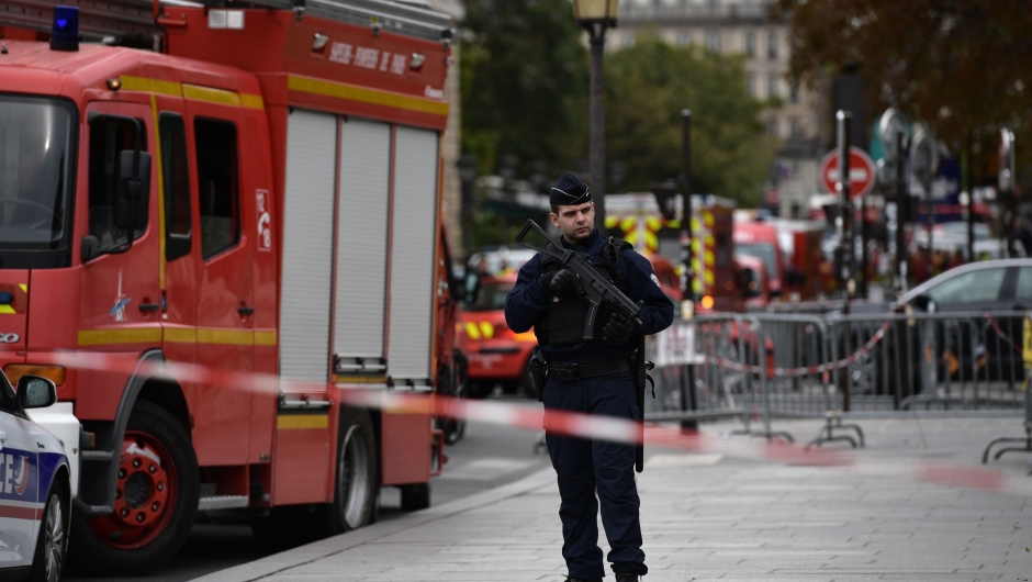A policeman stands next to firefighter vehicles near Paris prefecture de police (police headquarters) on October 3, 2019 after four officers were killed in a knife attack. - A knife attacker was shot dead after killing four officers at police headquarters in the historical centre of Paris on October 3, sources told AFP. (Photo by Martin BUREAU / AFP) (Photo by MARTIN BUREAU/AFP via Getty Images)
