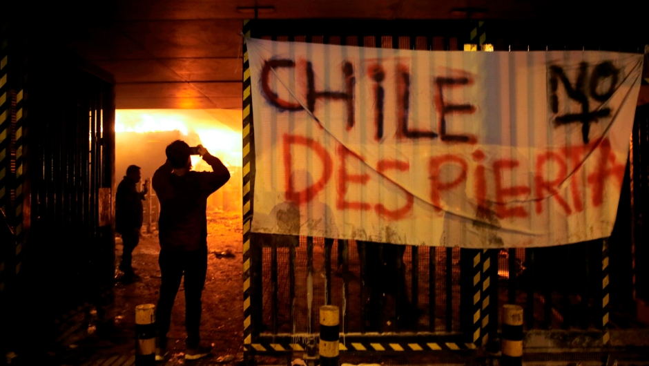 """TOPSHOT - People take pictures of Macul Metro station set on fire by protesters alongside a sign that reads """"Chile doesn't wake up"""" during a mass fare-dodging protest in Santiago, on October 19, 2019. - The entire Santiago Metro, which mobilizes about three million passengers per day, stopped operating on Friday afternoon following attacks in rejection of the rate hike, the company said. The chaos beat Santiago this Friday with confrontations, fires and attacks on the metropolitan railway, in protest of the increase in fares that forced the closure of all Metro stations. (Photo by JAVIER TORRES / AFP) (Photo by JAVIER TORRES/AFP via Getty Images)"""