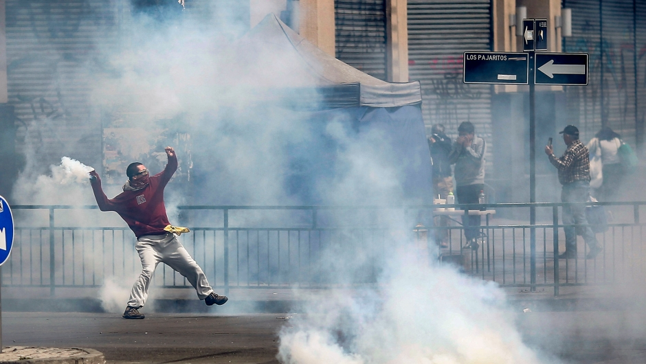 TOPSHOT - A demonstrators throws a tear gas can during clashes between protesters and the police at Plaza de Maipu in Santiago, on October 19, 2019. - Chile's president declared a state of emergency in Santiago Friday night and gave the military responsibility for security after a day of violent protests over an increase in the price of metro tickets. (Photo by Pablo VERA / AFP) (Photo by PABLO VERA/AFP via Getty Images)