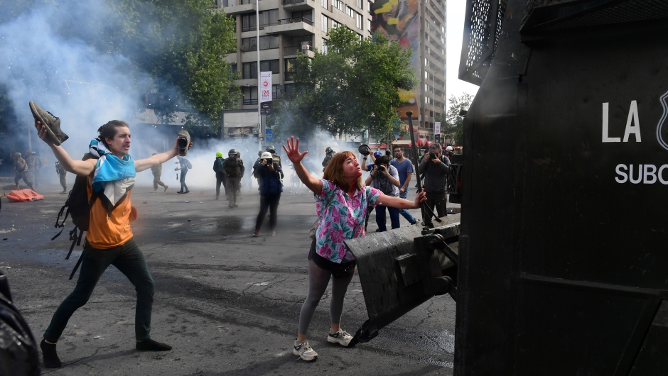 Demonstrators clash with riot police and army members in Santiago, on October 19, 2019. - Chile's president declared a state of emergency in Santiago Friday night and gave the military responsibility for security after a day of violent protests over an increase in the price of metro tickets. (Photo by Martin BERNETTI / AFP) (Photo by MARTIN BERNETTI/AFP via Getty Images)