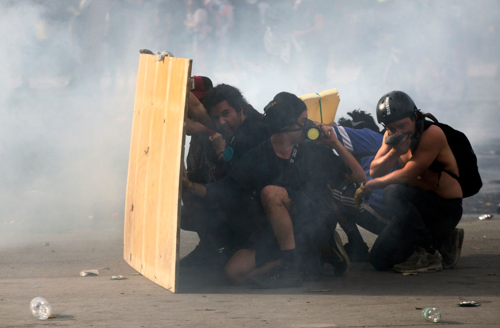 OPSHOT - Demonstrators clash with riot police on the fifth straight day of street violence which erupted over a now suspended hike in metro ticket prices, in Santiago, on October 22, 2019. - President Sebastian Pinera held a meeting with leaders of some of Chile's opposition parties on Tuesday, aiming to find a way to end street violence that has claimed 15 lives amid sustained protests. (Photo by CLAUDIO REYES / AFP) (Photo by CLAUDIO REYES/AFP via Getty Images)
