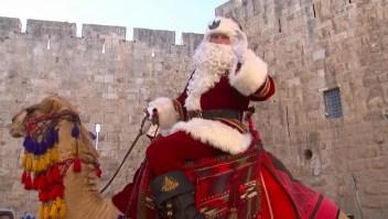 Papá Noel, en un camello, entrega árboles de Navidad