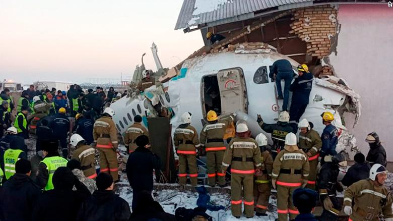 In this handout photo provided by the Emergency Situations Ministry of the Republic of Kazakhstan, police and rescuers work on the side of a plane crash near Almaty International Airport, outside Almaty, Kazakhstan, Friday, Dec. 27, 2019. Almaty International Airport said seven people died on Friday in the crash of a Bek Air plane in Kazakhstan. The aircraft had 100 passengers and crew abroad, and hit a concrete fence and a two-story building shortly after takeoff. ( Emergency Situations Ministry of the Republic of Kazakhstan photo via AP)