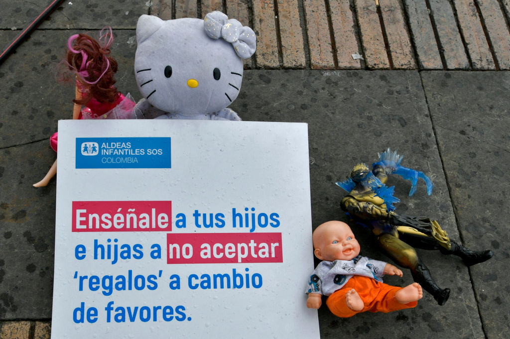 """Toys are displayed next to a sign reading """"Teach your children not to accept presents in exchange of favours"""" at the Bolivar square in Bogota, on November 20, 2019, as part of a campaign to raise awareness against child abuse during the universal Children's Day. - World Children's Day was first established in 1954 and is celebrated on November 20th to promote international awareness among children worldwide and improving their welfare. (Photo by Raul ARBOLEDA / AFP) (Photo by RAUL ARBOLEDA/AFP via Getty Images)"""