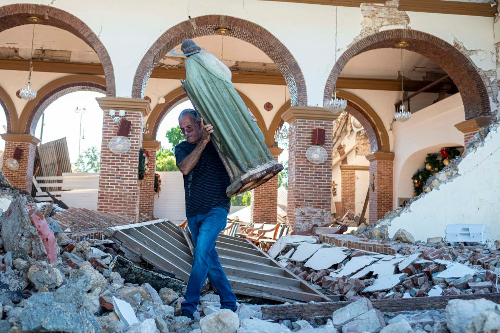 A man carries a St. Jude statue from the Inmaculada Concepcion church ruins that was built in 1841 and collapsed after an  earthquake hit the island in Guayanilla, Puerto Rico on January 7, 2020. - A strong earthquake struck south of Puerto Rico early January 7, 2020 followed by major aftershocks, the US Geological Survey said, the latest in a series of tremors that have shaken the island since December 28. The shallow 6.4 magnitude quake struck five miles (eight kilometers) south of the community of Indios, the USGS said, revising down its initial reading of 6.6. (Photo by Ricardo ARDUENGO / AFP) (Photo by RICARDO ARDUENGO/AFP via Getty Images)