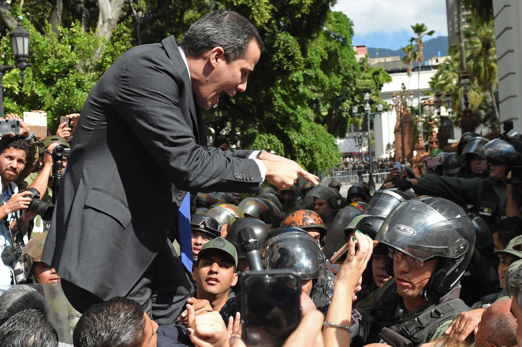 """Venezuelan opposition leader and self-proclaimed acting president Juan Guaido confronts Bolivarian National Guard members upon arrival at the National Assembly, in Caracas, on January 7, 2020. - Opposition leader Juan Guaido and a rival lawmaker, Luis Parra -who both had claimed to be Venezuela's parliament speaker, following two separate votes and accusations of a """"parliamentary coup- called for a parliamentary session today. (Photo by Cristian Hernandez / AFP) (Photo by CRISTIAN HERNANDEZ/AFP via Getty Images)"""