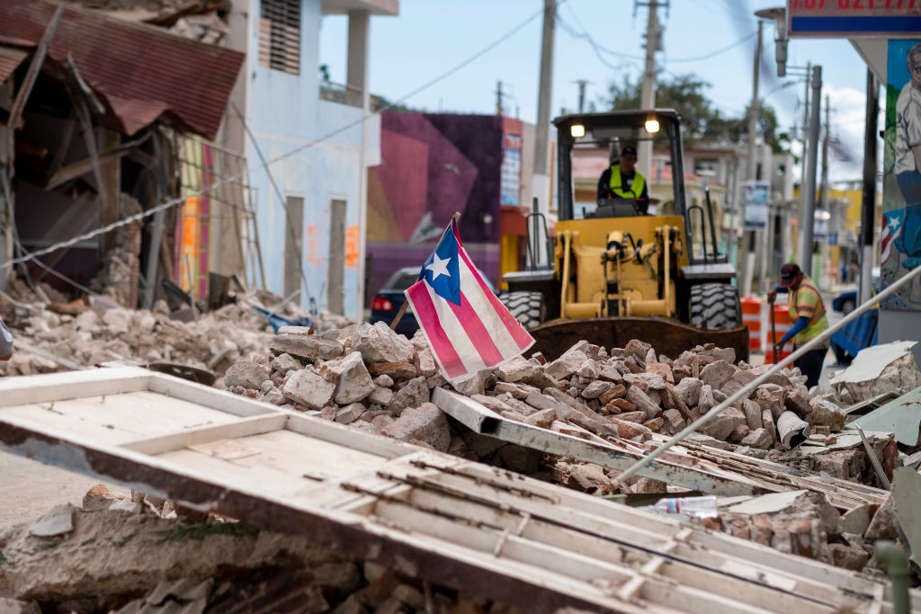 A Puerto Rican flag waves on top of a pile of rubble as debris is removed from a main road in Guanica, Puerto Rico on January 8, 2020, one day after the earthquake. - Puerto Rico's governor declared a state of emergency on Tuesday after a powerful 6.4 magnitude earthquake killed at least one person in the south of the island and caused widespread damage. Governor Wanda Vazquez said the declaration would allow for the activation of National Guard troops in the US territory still recovering from a devastating 2017 hurricane. (Photo by Ricardo ARDUENGO / AFP) (Photo by RICARDO ARDUENGO/AFP via Getty Images)