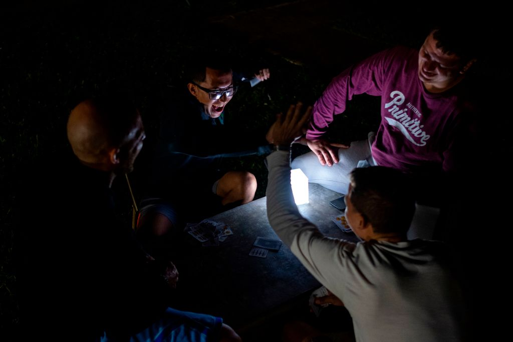 A group of young men play cards in the outdoors lit by a solar rechargeable lamp after an earthquake hit the island in Guanica, Puerto Rico on January 8, 2020. - Puerto Rico's governor declared a state of emergency on Tuesday after a powerful 6.4 magnitude earthquake killed at least one person in the south of the island and caused widespread damage. Governor Wanda Vazquez said the declaration would allow for the activation of National Guard troops in the US territory still recovering from a devastating 2017 hurricane. (Photo by Ricardo ARDUENGO / AFP) (Photo by RICARDO ARDUENGO/AFP via Getty Images)