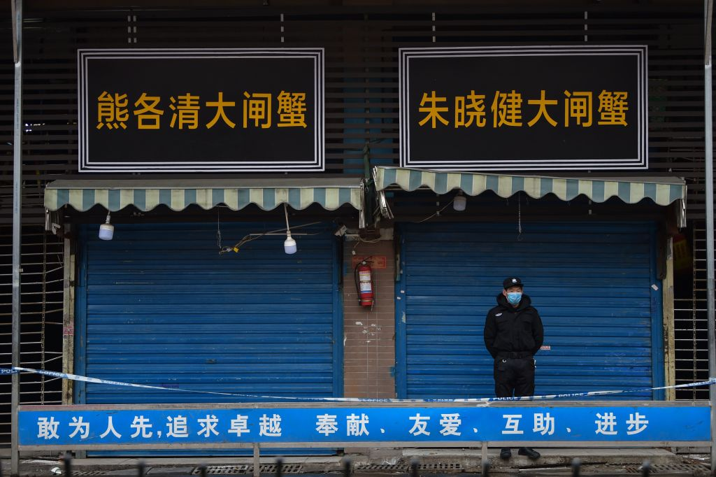 TOPSHOT - A security guard stands outside the Huanan Seafood Wholesale Market where the coronavirus was detected in Wuhan on January 24, 2020 - The death toll in China's viral outbreak has risen to 25, with the number of confirmed cases also leaping to 830, the national health commission said. (Photo by Hector RETAMAL / AFP) (Photo by HECTOR RETAMAL/AFP via Getty Images)