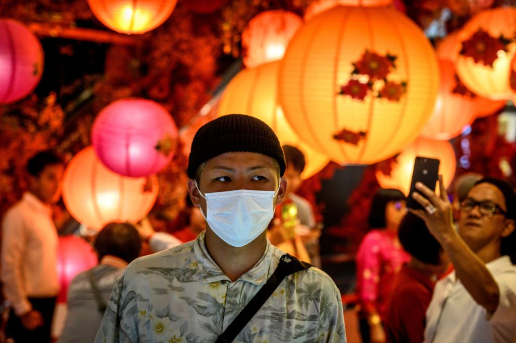 A man with a face mask walks in a shop decorated for the Chinese Lunar New Year in Bangkok on January 24, 2020, after four people were detected with the Coronavirus in Thailand. (Photo by Mladen ANTONOV / AFP) (Photo by MLADEN ANTONOV/AFP via Getty Images)