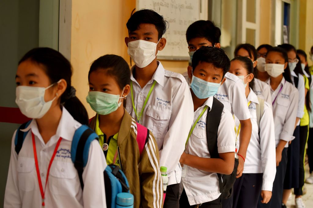 TOPSHOT - Mask-clad students line up to disinfect their hands with an alcohol solution before entering class at a school in Phnom Penh on January 28, 2020. - Cambodia's health ministry reported the country's first case of the deadly coronavirus on January 27. The virus, which can cause a pneumonia-like acute respiratory infection, has in a matter of weeks killed more 106 people and infected more than 4,000 in China, while cases have been identified in more than a dozen other countries. (Photo by TANG CHHIN Sothy / AFP) (Photo by TANG CHHIN SOTHY/AFP via Getty Images)