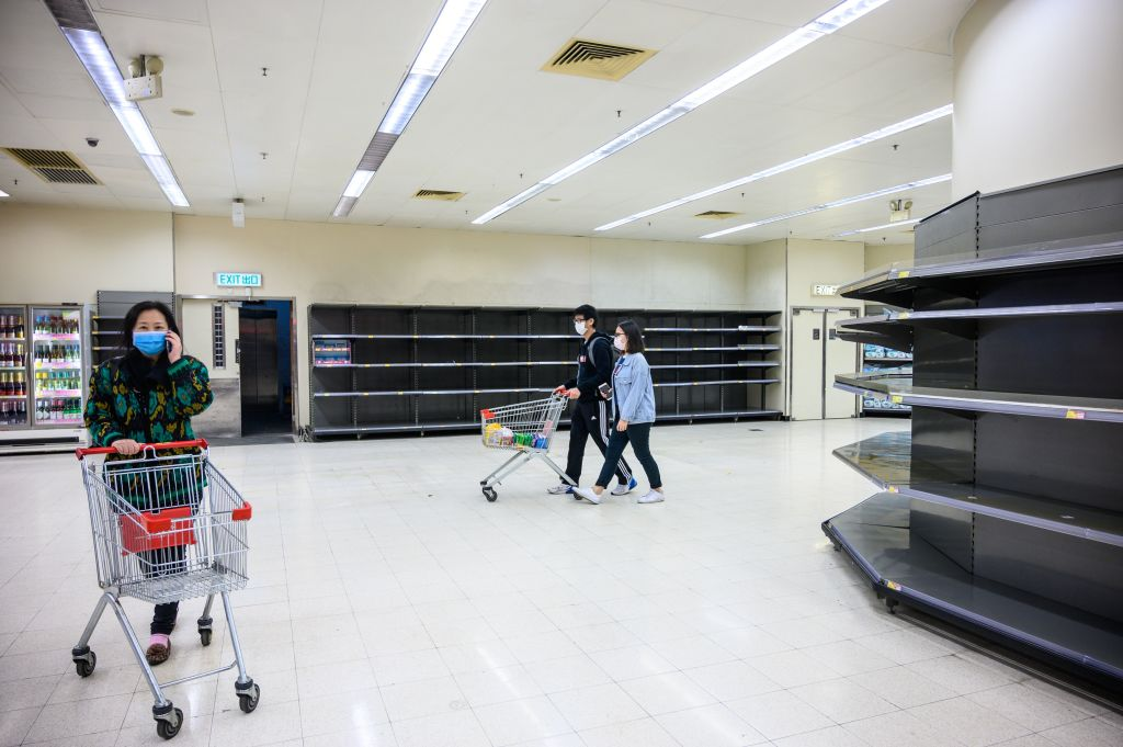 TOPSHOT - Shoppers wearing protective facemasks walk past bare supermarket shelves, usually stocked with toilet paper and kitchen rolls, in Hong Kong on February 6, 2020. - Panic buyers in Hong Kong have descended on supermarkets to snap up toilet paper after false online claims of shortages, prompting authorities to appeal for calm as the city's seven million residents fret about a deadly coronavirus outbreak. (Photo by Philip FONG / AFP) (Photo by PHILIP FONG/AFP via Getty Images)