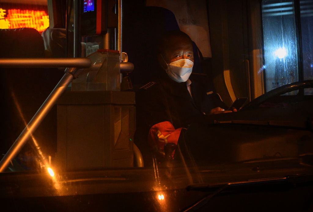 BEIJING, CHINA - FEBRUARY 13: A Chinese bus driver wears a protective mask as he waits in his bus on February 13, 2020 in Beijing, China. The number of cases of the deadly new coronavirus COVID-19 rose to more than 52000 in mainland China Thursday, in what the World Health Organization (WHO) has declared a global public health emergency. China continued to lock down the city of Wuhan in an effort to contain the spread of the pneumonia-like disease which medicals experts have confirmed can be passed from human to human. In an unprecedented move, Chinese authorities have maintained and in some cases tightened the travel restrictions on the city which is the epicentre of the virus and also in municipalities in other parts of the country affecting tens of millions of people. The number of those who have died from the virus in China climbed to over 1300 on Thursday, mostly in Hubei province, and cases have been reported in other countries including the United States, Canada, Australia, Japan, South Korea, India, the United Kingdom, Germany, France and several others. The World Health Organization has warned all governments to be on alert and screening has been stepped up at airports around the world. Some countries, including the United States, have put restrictions on Chinese travellers entering and advised their citizens against travel to China. (Photo by Kevin Frayer/Getty Images)