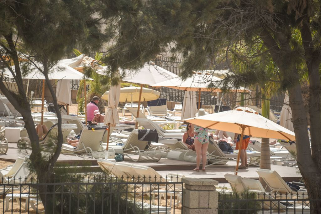 Tourists sunbath at the H10 Costa Adeje Palace Hotel in La Caleta, on February 25, 2020, where hundreds of people were confined after an Italian tourist was hospitalised with a suspected case of coronavirus. - Tourists staying in a four-star hotel on the Spanish island of Tenerife, in the Canary archipielago, were confined to their rooms today following the announcement of a suspected novel coronavirus, COVID-19, case waiting for official confirmation. This possible case was detected yesterday in Tenerife, where an Italian national passed a first test which turned out to be positive, announced the Spanish Ministry of Health. (Photo by DESIREE MARTIN / AFP) (Photo by DESIREE MARTIN/AFP via Getty Images)