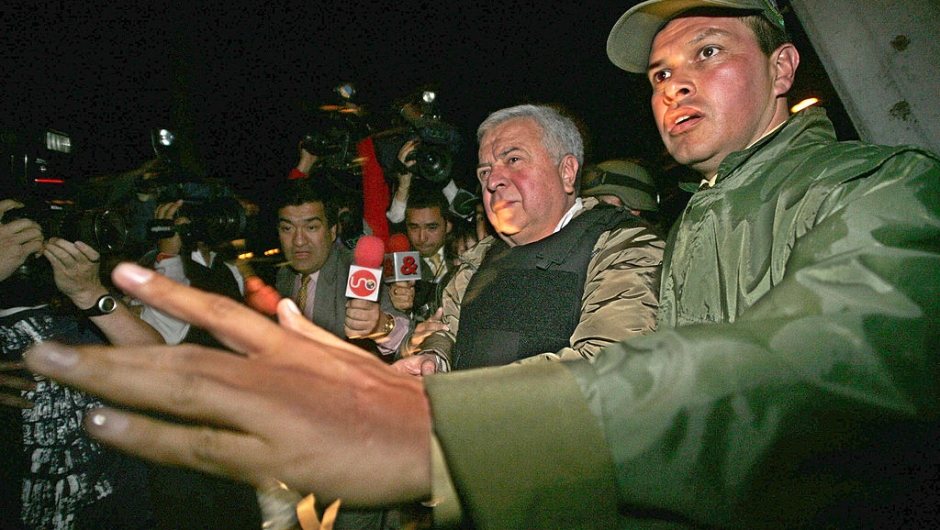 """BOGOTA, COLOMBIA: Gilberto Rodriguez Orejuela (L), head of the Cali drug cartel, is escorted at the narcotic-police airport in Bogota, to a plane that will take him in extradition to the United States, 03 December 2004. Colombian President Alvaro Uribe gave earlier in the day his final approval of Rodriguez Orejuela's deportation - and his handover to the US Drug Enforcement Administration . The wily 64-year-old drug kingpin nicknamed """"The Chess Player"""" has been in detention since 1995. He and his bother Miguel headed one of the largest drug trafficking organizations in the world. AFP PHOTO/Luis ACOSTA (Photo credit should read LUIS ACOSTA/AFP via Getty Images)"""
