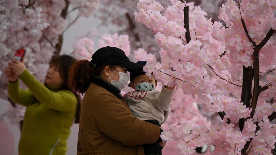 """TOPSHOT - People wearing facemasks are seen near a mall in Nanjing, east China's Jiangsu Province on March 12, 2020. - The new coronavirus outbreak """"is a controllable pandemic"""" if countries step up measures to tackle it, the head of the World Health Organization said. (Photo by NOEL CELIS / AFP) (Photo by NOEL CELIS/AFP via Getty Images)"""