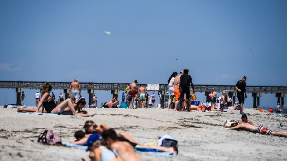 People relax on the Beach amid the Coronavirus pandemic in Tybee Island, Georgia on April 25, 2020. - After being locked down for weeks, many residents in Georgia are thumbing their noses at the deadly coronavirus and seeking sanctuary in the sun, sand and waves of the southern state's beaches. Under a cloudless blue sky with balmy temperatures and soft breezes rolling off the water, Tybee Island proved a powerful weekend lure Saturday for Georgians desperate for any return to normalcy -- and an escape from self-imposed isolation. (Photo by CHANDAN KHANNA / AFP) (Photo by CHANDAN KHANNA/AFP via Getty Images)