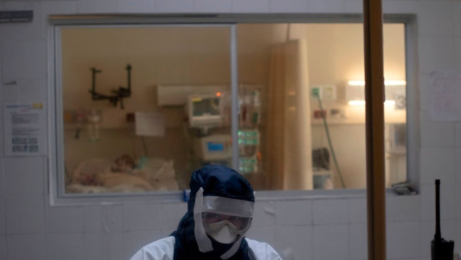 """A doctor remains in an observation cabin in front of a patient infected with the novel coronavirus COVID-19, in the intensive care unit of the San Rafael Hospital in Santa Tecla, La Libertad, just 10 km from the Salvadorean capital San Salvador, on May 16, 2020. - The San Rafael Hospital, which has been assigned to care for 100 COVID-19 patients whose cases range from """"severe to critical,"""" is leading in their recovery, and part of the success, according to hospital director Yeerles Luis Ramirez, has been early treatment. (Photo by Yuri CORTEZ / AFP) (Photo by YURI CORTEZ/AFP via Getty Images)"""