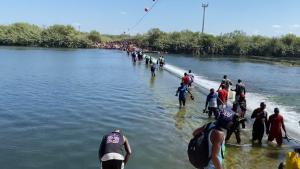 Mira a decenas de migrantes cruzar el río Bravo a EE.UU.